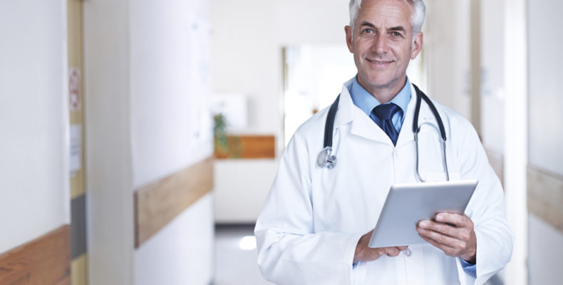 Portrait of a mature male doctor standing with a digital tablet in a hospital corridor